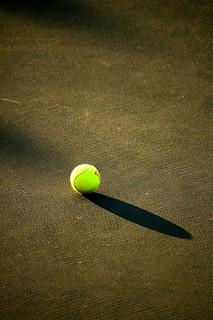 影が長く伸びたテニスボール