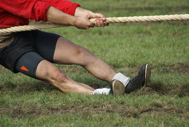 綱引きに勝つために、地面に足が食い込むほどに必死に縄を引いている男性