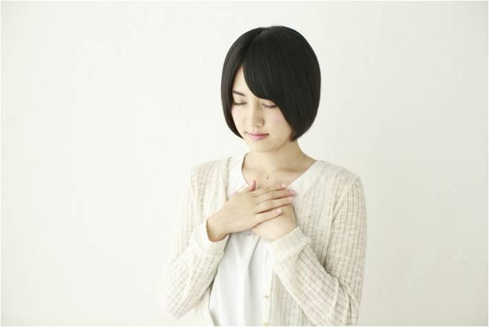 胸に手を当て、自分の内面を見つめ、自分自身と触れあう女性