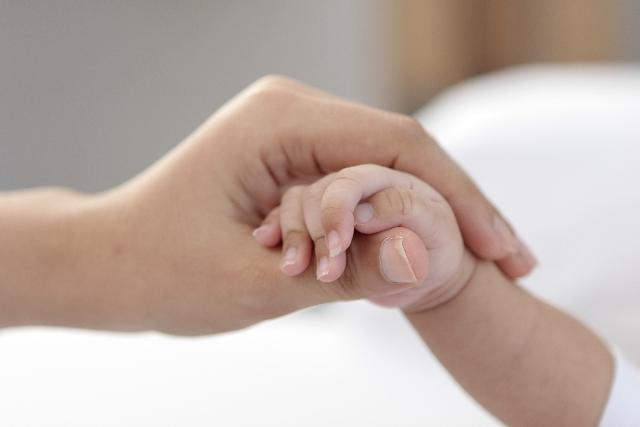 赤ちゃんの手に優しく触れる、母親の手