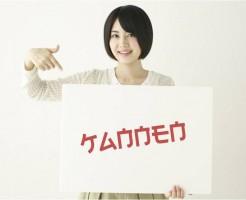 カタカナに似ているけれども読めない文字が書かれたボードを持つ女性(日本人だけに読めないフォント)