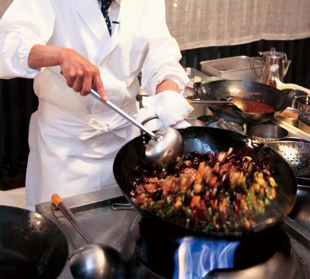 中華鍋で料理をつくるコックさん