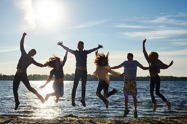 信頼関係で結ばれた仲間たちのイメージ(水際で飛び跳ねて遊ぶ若者たち)