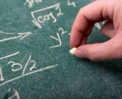 数式が書かれた黒板とチョークを持つ手